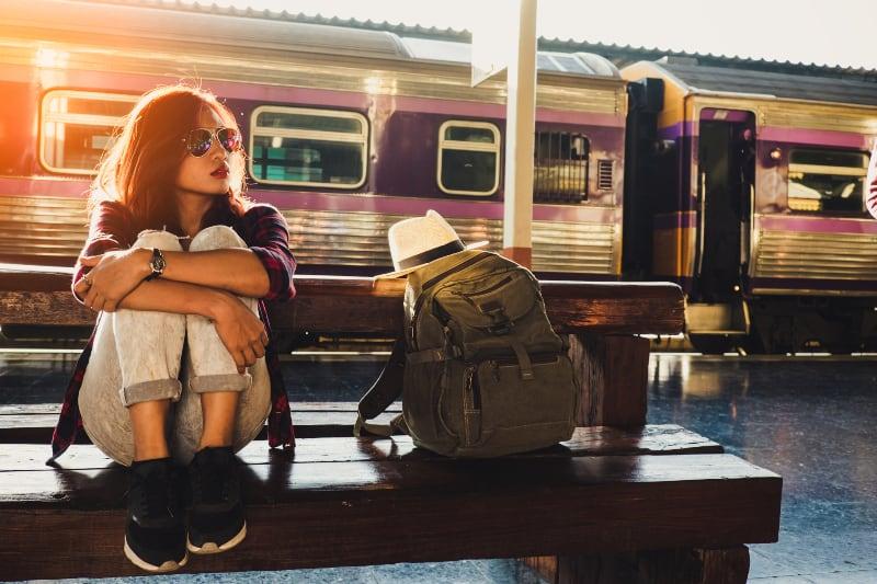ein junges Mädchen wartet auf einen Zug