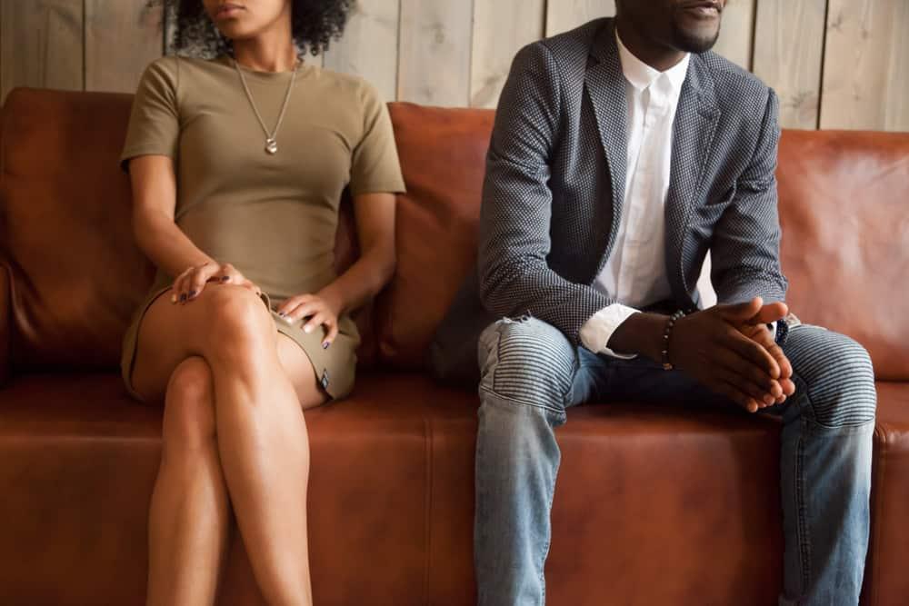 ein unglückliches afrikanisches Paar, das auf einer Ledercouch sitzt