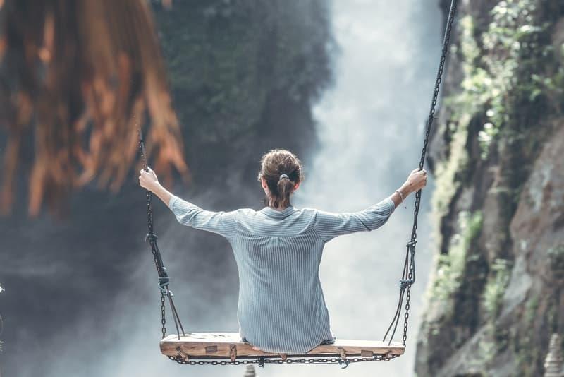 eine Frau auf einer Schaukel über dem Canyon