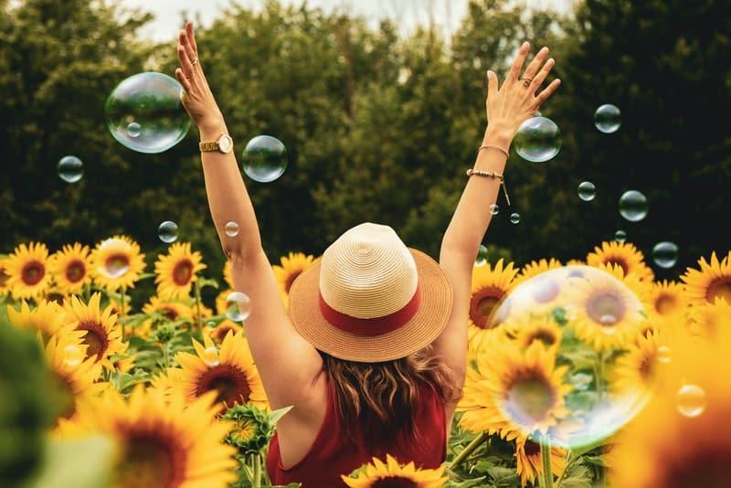 eine Frau, die mit ausgestreckten Armen in einer Sonnenblume steht