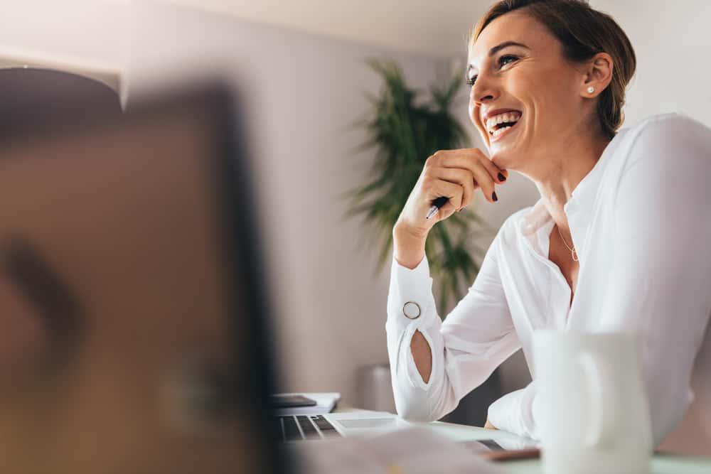 eine lächelnde Geschäftsfrau, die an einem Schreibtisch sitzt