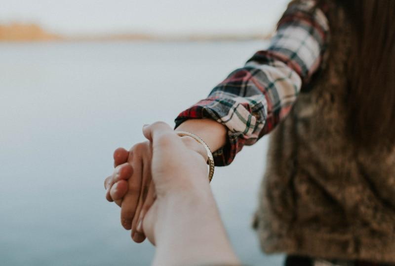 flache Fokusfotografie von Mann und Frau, die Hände halten