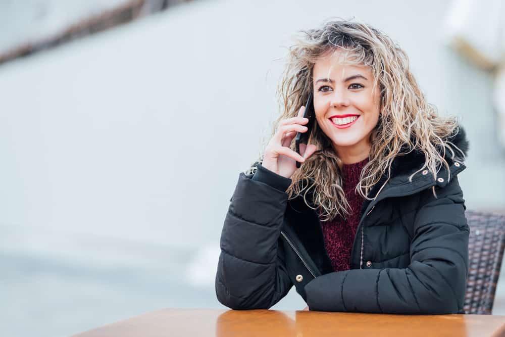 glückliche Frau in der Winterjacke, die am Handy sitzt und spricht