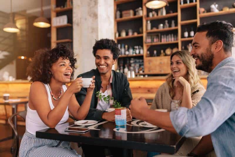 glückliche junge Freunde, die Unterhaltung im Café haben