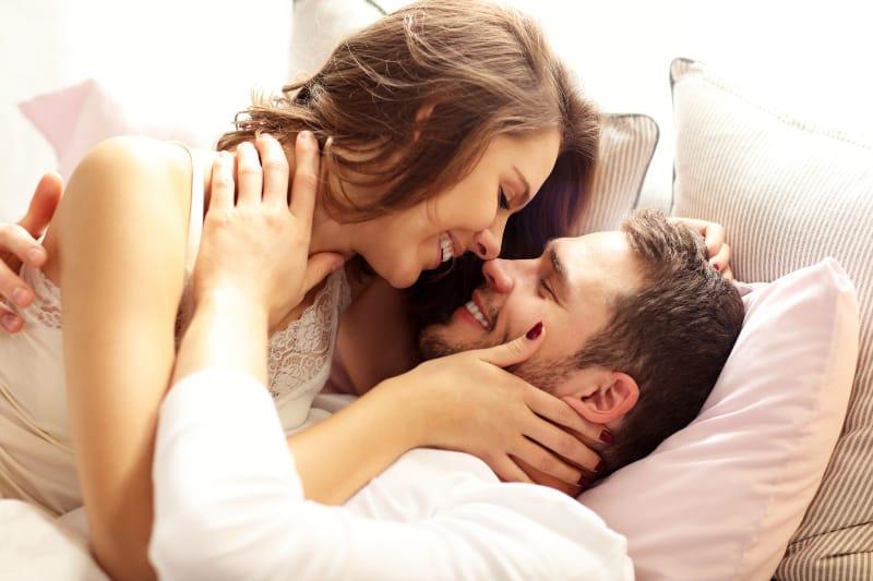 junge Frau küsst ihren Mann im Bett