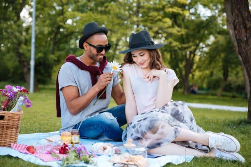 lächelnder junger Mann, der seiner schüchternen Freundin beim Picknick Blume gibt