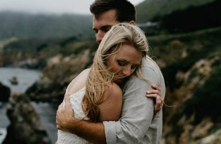 Das Mädchen umarmt den jungen Mann oben auf dem Hügel nebenan