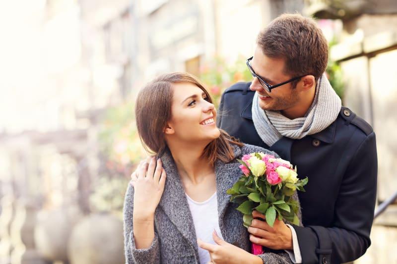 Ein Mann gibt einem Mädchen eine bunte Rose