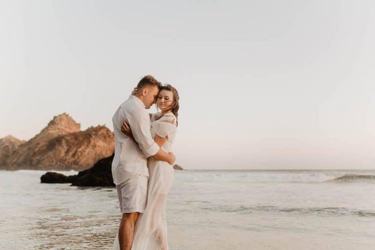 Ein Mann umarmt ein Mädchen in einem weißen Kleid