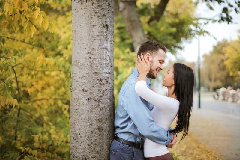 Ein Mann und eine Frau umarmen sich unter einem Baum