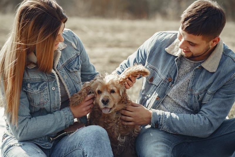 Ein Paar in Texas Jacken sitzt mit einem braunen Hund