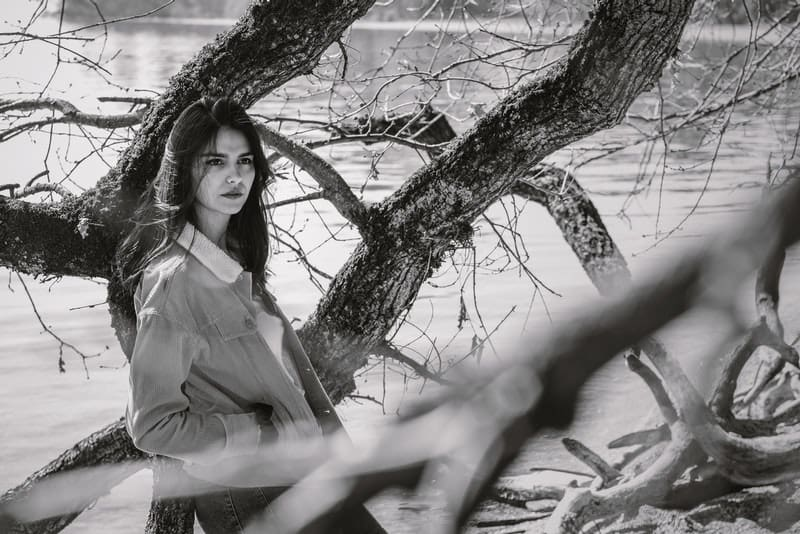Eine Frau in Jeansjacke lehnt an einem Baum