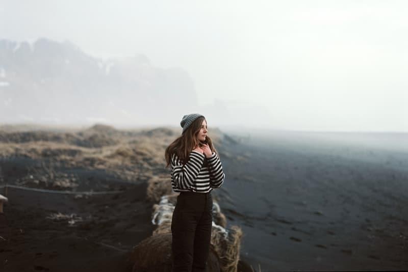 Eine Frau mit einer Mütze steht auf einem Felsen oben auf einem Hügel