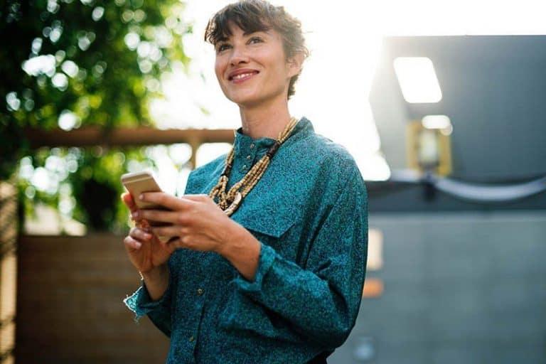Eine sichtlich launische Frau hält ihr Handy in den Händen