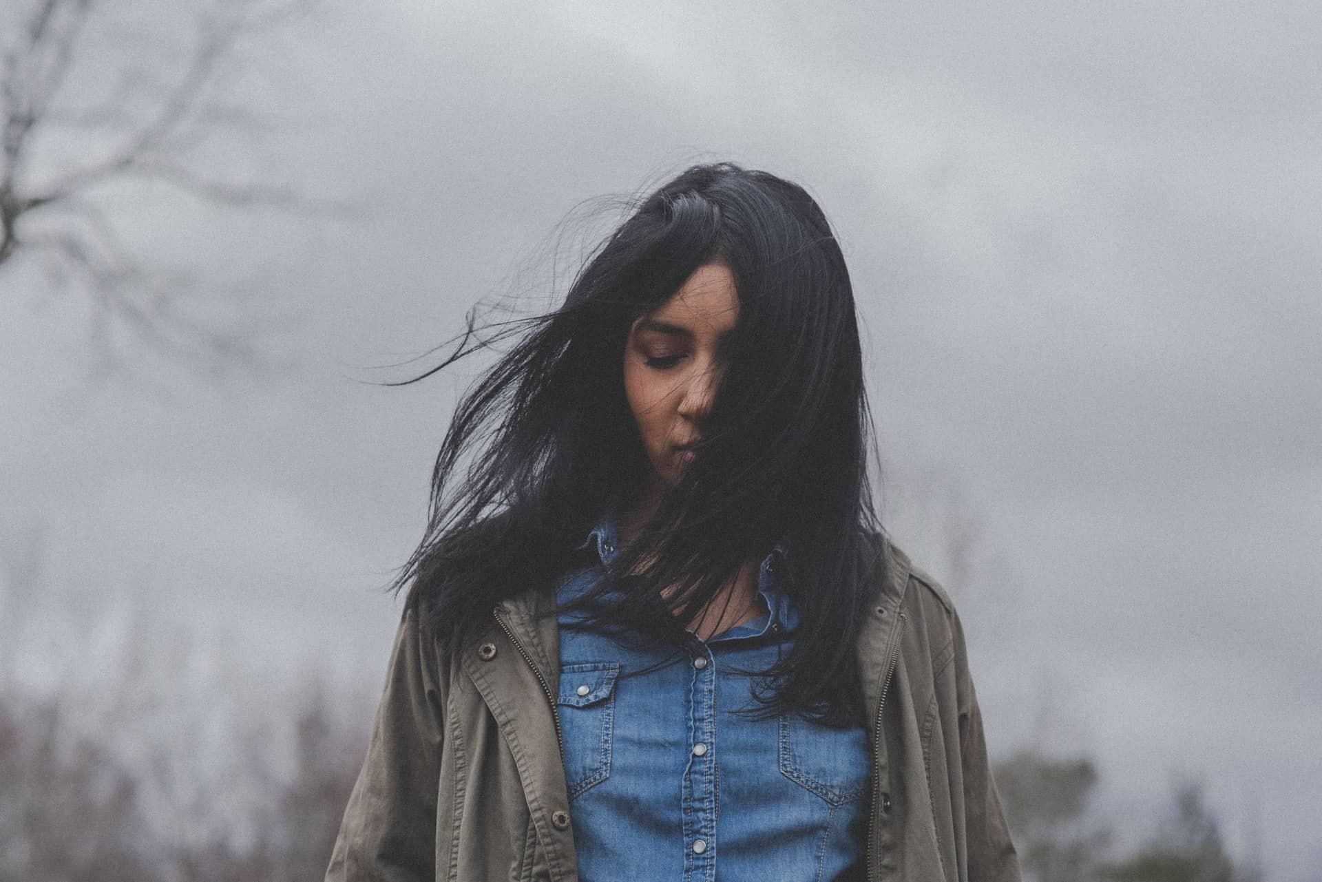 Eine traurige Brünette steht draußen im Wind, der ihre Haare trägt