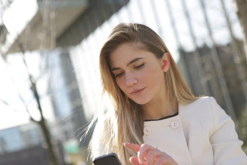 Eine traurige Frau auf der Straße benutzt das Telefon