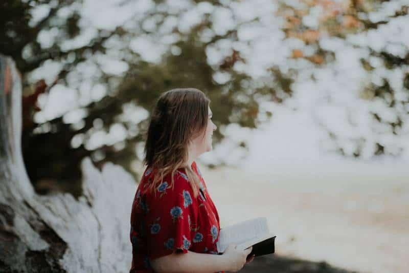 Frau hält Buch im Freien
