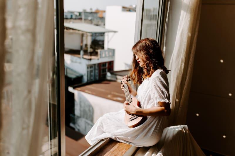 Frau sitzt am Fenster im Zimmer