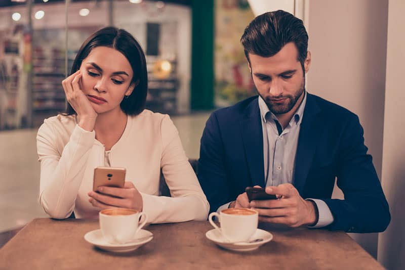 Gelangweiltes Paar, das in einem Café sitzt, das Telefone hält