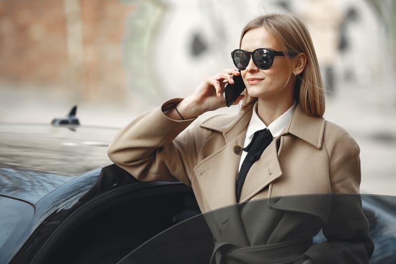 Geschäftsfrau mit Sonnencreme, die am Telefon spricht