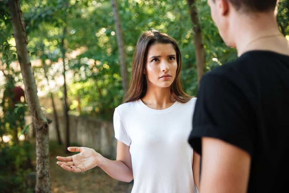 Im Park sagt ein Mädchen in einem weißen T-Shirt wütend etwas zu einem Mann