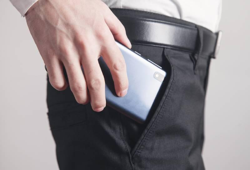 Mann, der Smartphone in Hosentasche setzt.