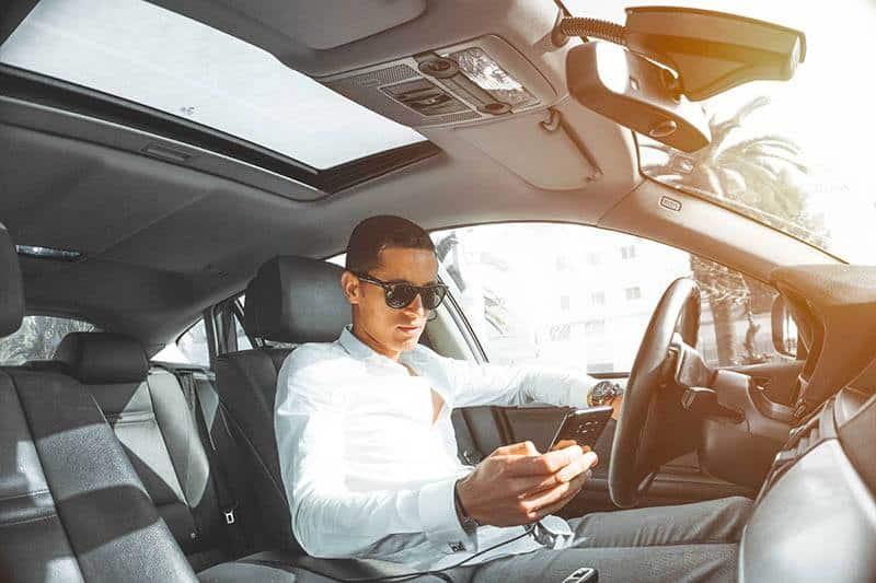 Mann, der Sonnenbrille und blaues Hemd trägt, das auf seinem Telefon tippt