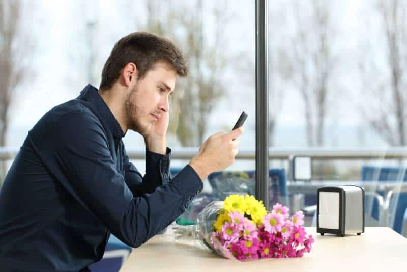 Mann, der Telefon unglücklich ansieht