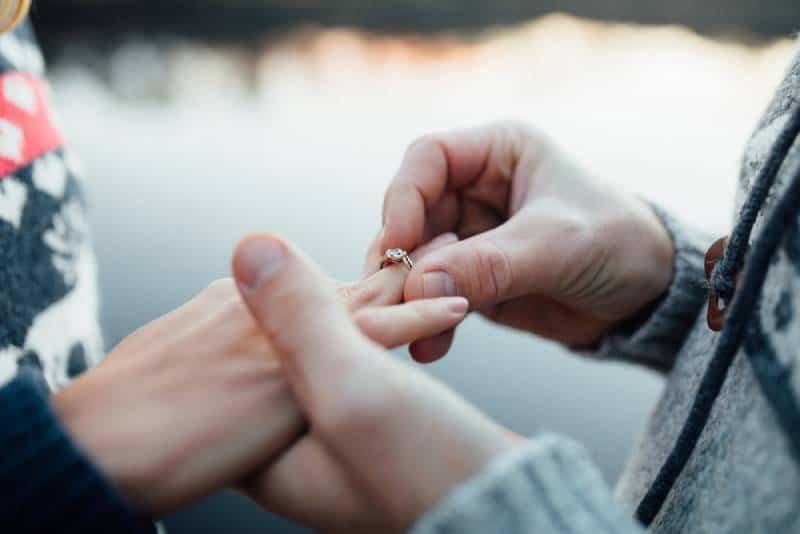 Mann, der Verlobungssilberring auf Frauenhand setzt