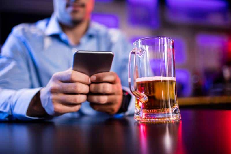 Mann mit Handy am Bartheke in der Bar
