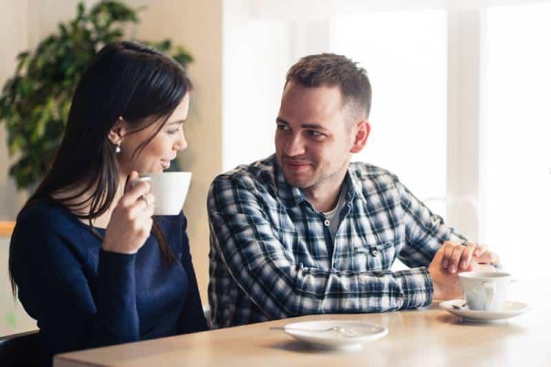 Mann und Frau unterhalten sich im Café und trinken Tee