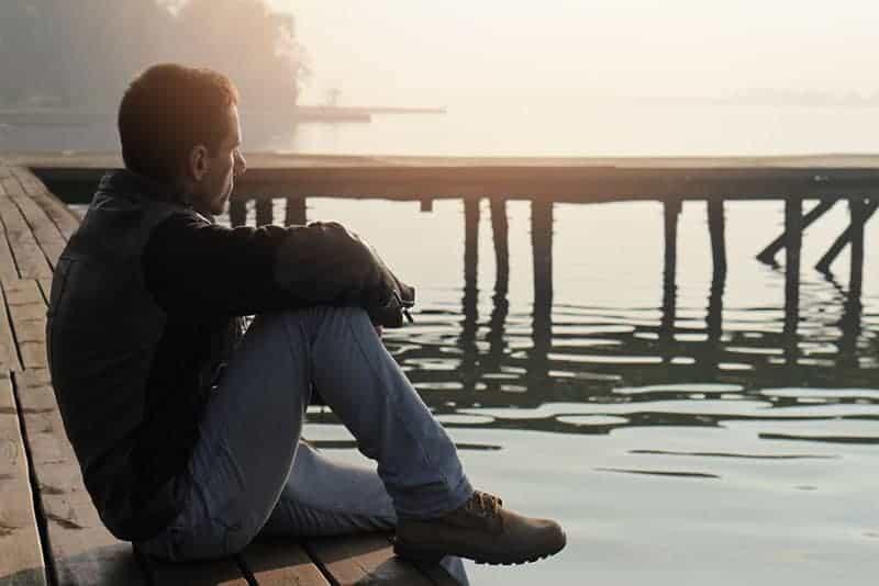Seitenansicht des Mannes, der auf Holzdock neben Wasser sitzt