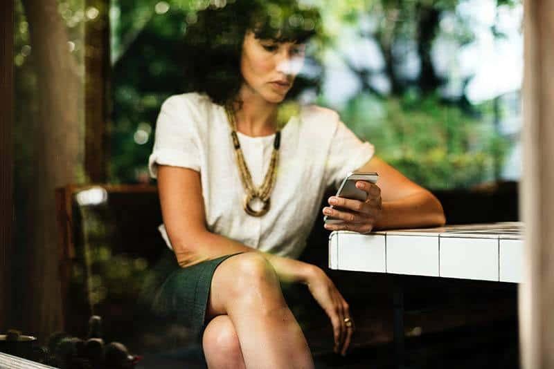 Eine Frau in einem Rock sitzt in einem Café und schaut auf ihr Handy