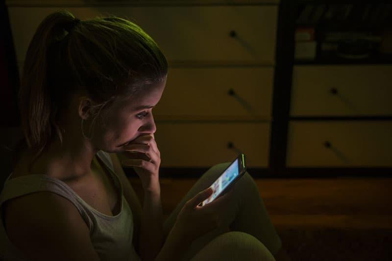 besorgte Frau, die nachts auf ihrem Telefon tippt