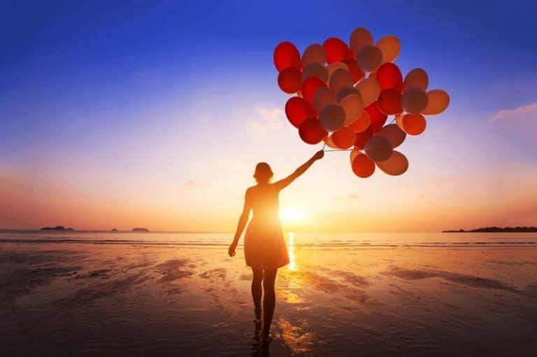 ein Mädchen, das Hunderte von Luftballons in der Hand hält