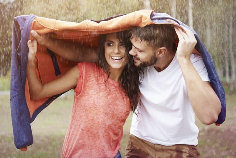 ein Paar versteckt sich unter einer Regenjacke