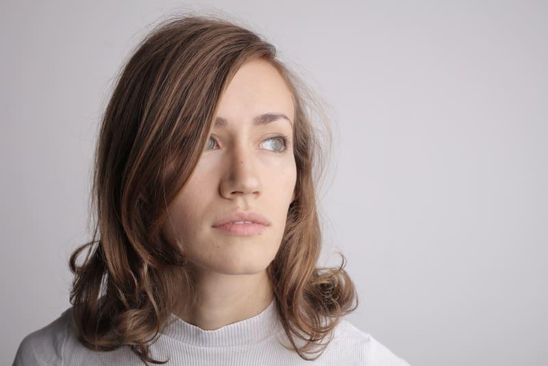 ein Porträt einer braunhaarigen traurigen Frau