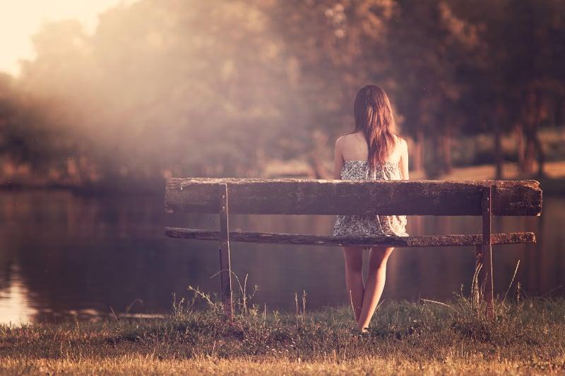 ein einsames Mädchen sitzt auf einer Bank