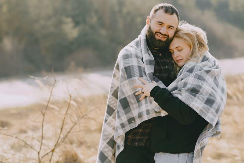 ein romantisches Paar unter einer Decke, die in einem Weizenfeld steht