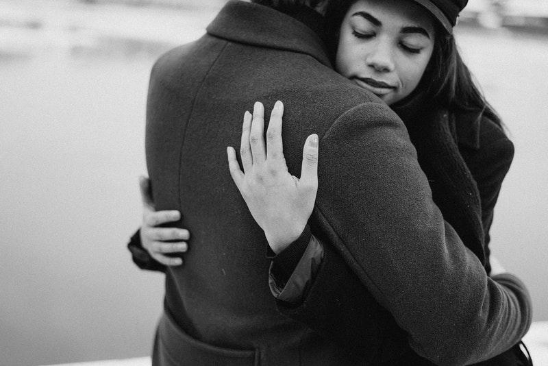 eine Frau in den Armen eines Mannes in einem schwarzen Mantel