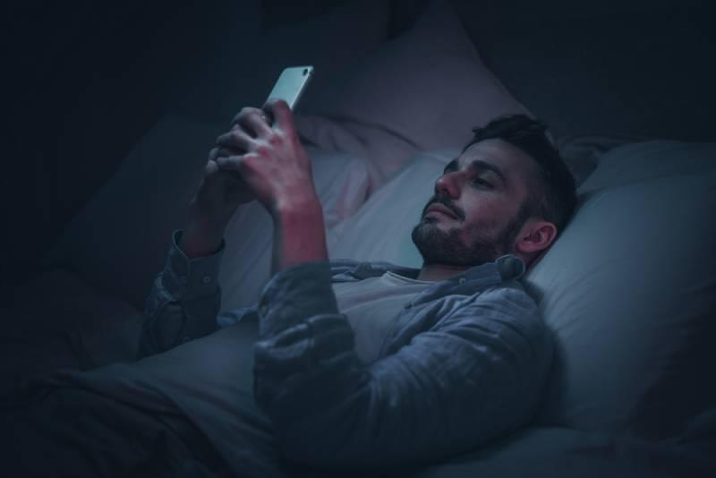 lächelnder Mann mit Smartphone vor dem Schlafengehen