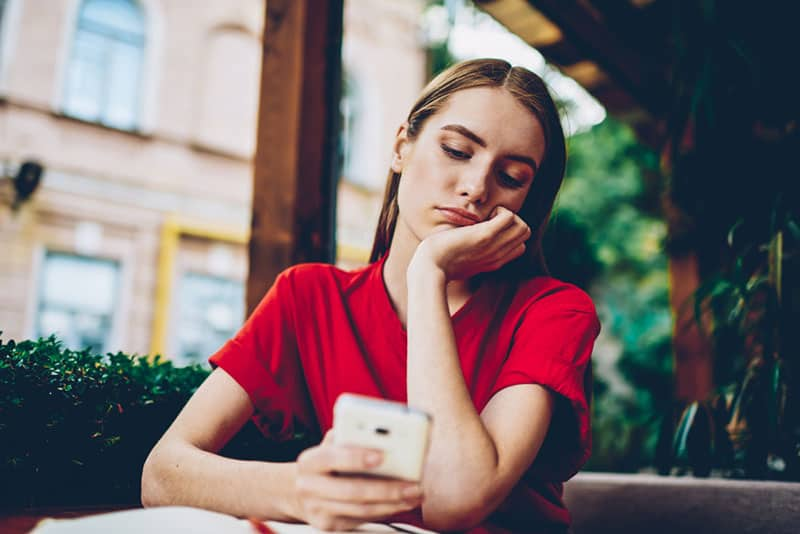 nachdenkliche Frau, die rotes T-Shirt trägt und ihr Telefon im Café betrachtet