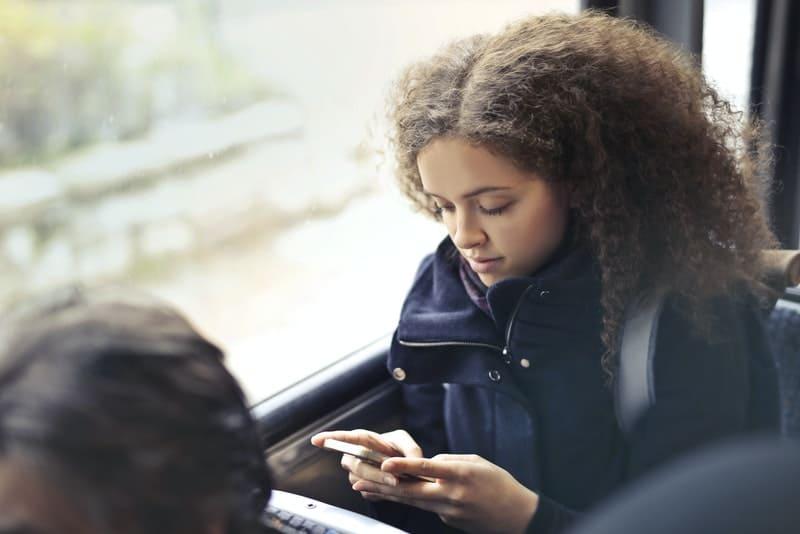 trauriges Mädchen schreibt SMS im Zug