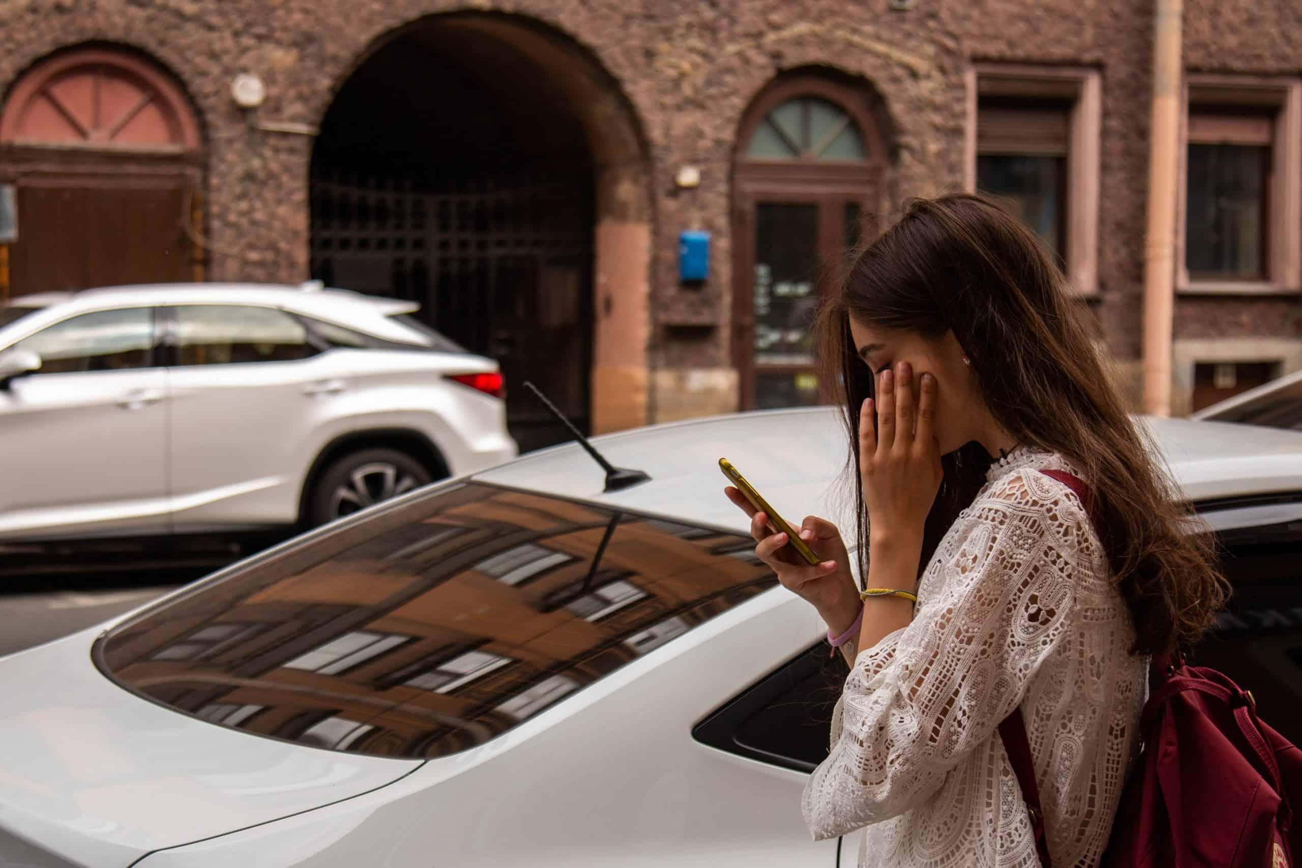Mädchen, das die Straße entlang geht und auf ihrem Handy spricht