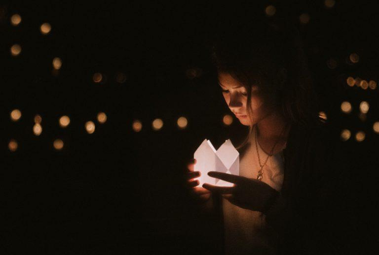 Das Mädchen hält eine Kerze in der Hand