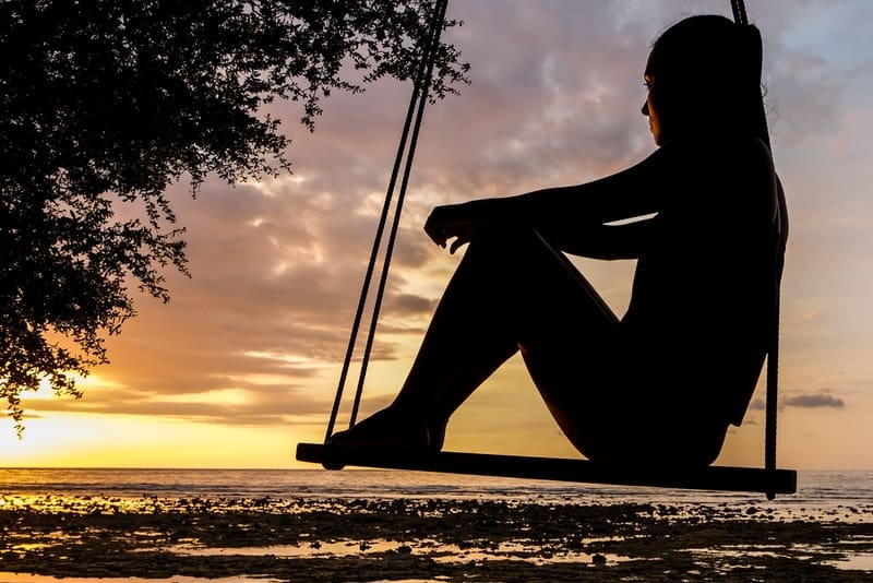 Das Mädchen sitzt auf einer Schaukel und beobachtet den Sonnenuntergang