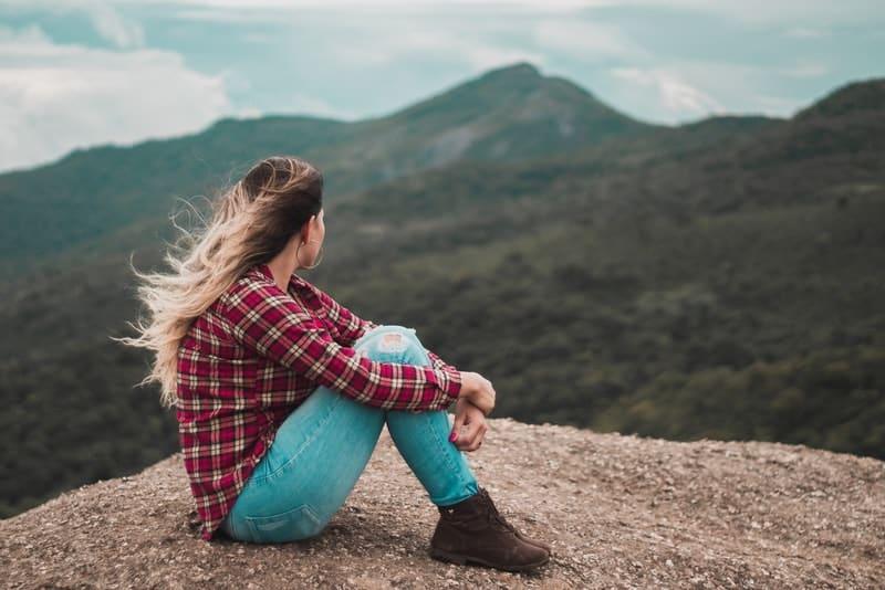 Ein Mädchen in einem karierten Hemd sitzt auf einem Felsen und beobachtet die Landschaft