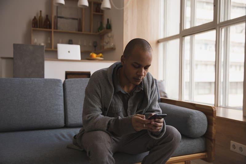 Ein Mann in einem grauen Pullover sitzt auf der Couch und schreibt eine SMS