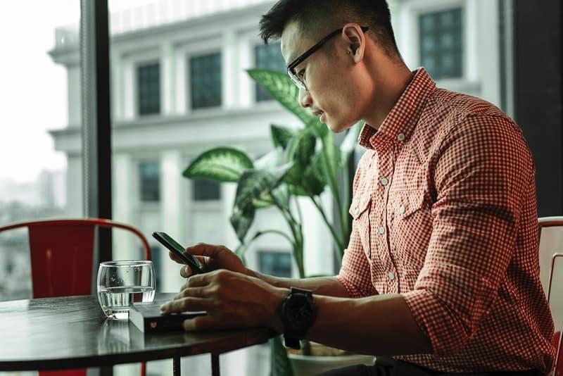 Ein Mann in einem karierten Hemd mit Brille benutzt ein Telefon