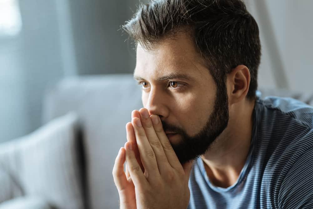 Ein Mann mit Bart in einem blauen T-Shirt hält die Hände vors Gesicht